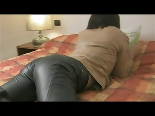 Girl posing in black leather pants and brown leather jacket